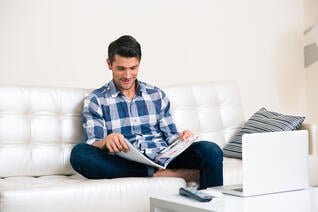 Portrait of a man reading magazine on the sofa at home
